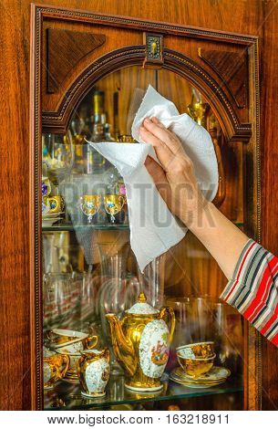Home cleaning. A woman uses a paper towel to wipe the glass of the cupboard.