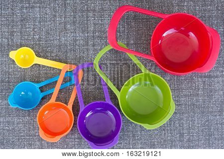 The colorful measuring cups on the flooor