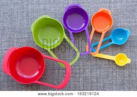The colorful measuring cups on the floor
