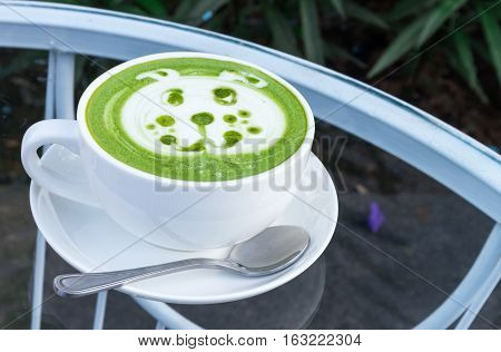 Hot matcha latte art with cute dog face cartoon on glass table