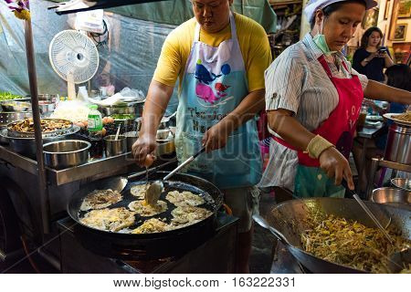 Hua Hin Thailand - December 28 2015: Man and woman making traditional pad thai and oyster omelette on Hua Hin Night Food Market. Authentic Thailand street food