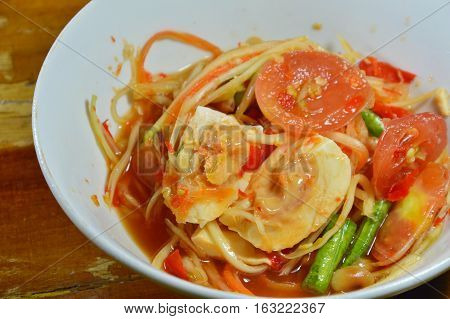 papaya spicy salad or Som Tum in Thai topping salty egg on bowl