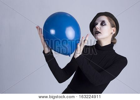 Young  beauty woman mime with blue ball