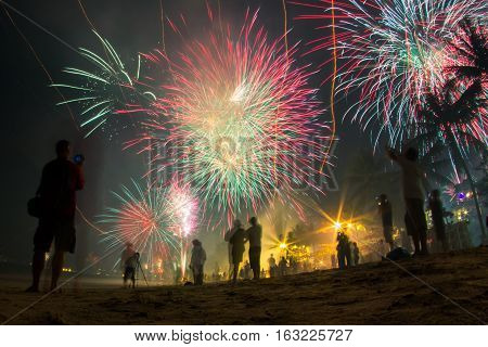 Amazing glorious fireworks on the beach with defocused people celebrating New Year