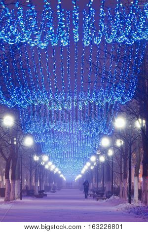 Beautiful Winter alley at night with Christmas garlands on it. Night illumination and lonely person in the alley