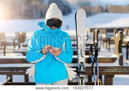 Woman In Ski Glasses Holding A Smartphone.