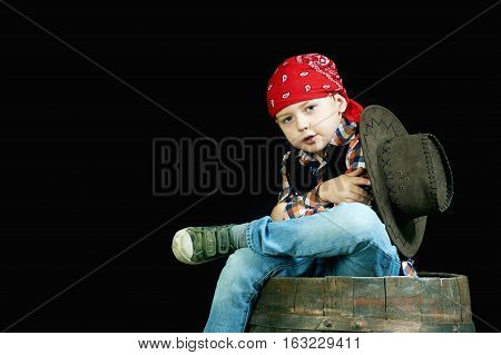 Cheerful little boy in a bandana and a plaid shirt on dark background in Studio
