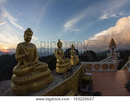 Statues of Buddha at Tiger Temple on the top of karst mount at sunset Krabi Province Thailand