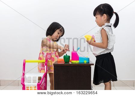 Asian Chinese Little Sisters Pretending Customer And Cashier With Trolley