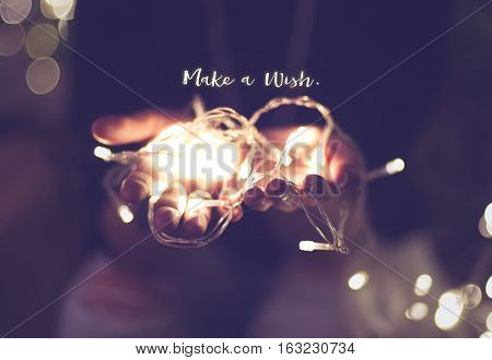 Make a wish word over hand with light bokeh in vintage filter,Holiday quote,christmas season