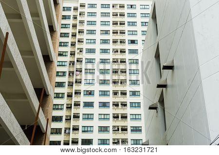 Old condominium between urban office buildings .