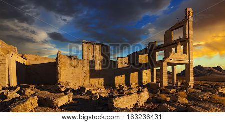 Rhyolite Nevada ghost town at sunrise with dramatic sky and shadows.