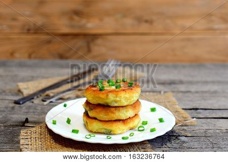 Vegetable patties on a plate, fork, knife on wooden table. Fried patties cooked of potatoes, green peas, carrot and green beans and garnished with fresh green onion. Delicious vegetable meal