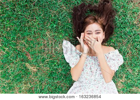 Smiling Happy Girl Lying Down On A Grass.