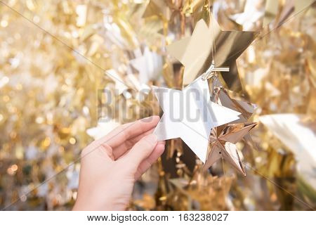 Gold and silver Christmas decorations in star shape on bokeh blur backgroung with golden light. Focus on blank star that woman's holding . Copy space.