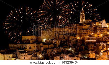 panoramic view of typical stones (Sassi di Matera) and church of Matera at night with golden abstract blinking sparkle celebration fireworks light