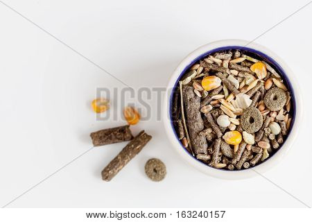 dry food for rodents in bowl on white background top view.