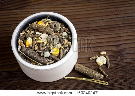 dry food for rodents in bowl on dark wooden background