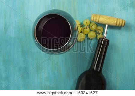 A vibrant photo of a glass of red wine with a bunch of grapes and a bottle with a corkscrew, shot from above on a turquoise blue wooden background texture, with copyspace