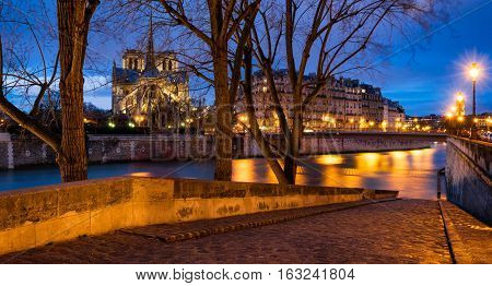 Twilight on Notre Dame de Paris cathedral and banks of Seine River from Ile Saint Louis. 4th Arrondissement Paris France