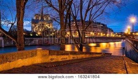 Twilight on Notre Dame de Paris cathedral and banks of Seine River from Ile Saint Louis. 4th Arrondissement Paris France