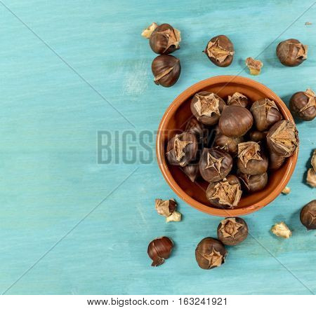 An overhead photo of peeled and unpeeled roasted chestnuts in an earthenware bowl, on a vibrant teal blue background with copyspace