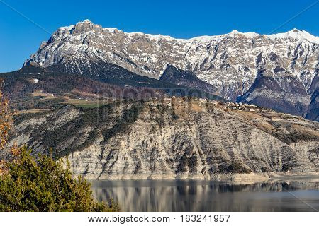 Village of Sauze du Lac on plateau with the Grand Morgon peak in the background and Serre Poncon Lake in winter. Hautes-Alpes French Alps France