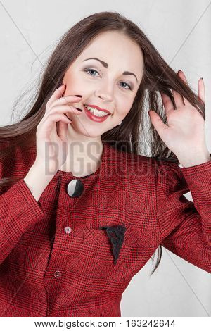 Portrait smiling young pretty woman in red jacket hand adjusts his hair
