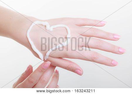 Beauty cosmetics concept. Cream on woman hand heart shape. Studio shot on white background