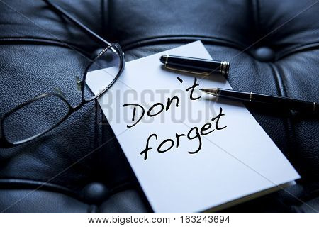 the words 'Don't forget' written on white paper next to eyeglasses and pen on black leather