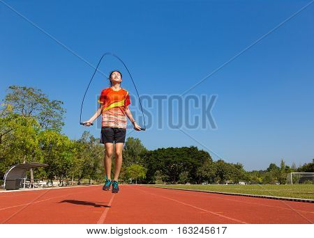 young female asian athlete rope jumping outdoor on running track at football or soccer field with trees and clear blue sky in background