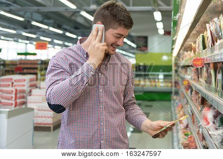 Handsome Man On Mobile Phone At Supermarket