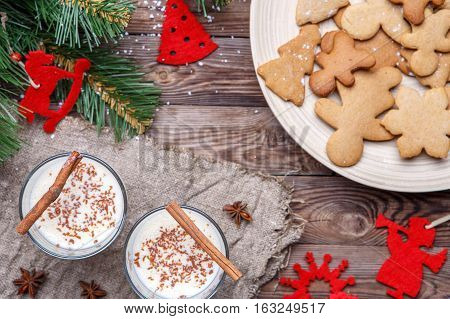 Christmas table with egg-flip on sackcloth, with cookies, Christmas tree branches