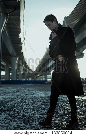 Young stylish woman urban walking under bridge