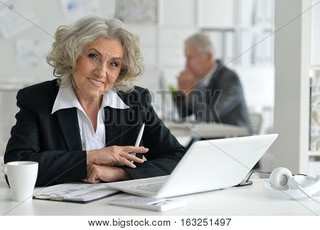 Portrait of senior businesswoman with laptop in the office