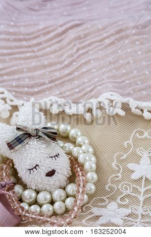 White brooch like head of hare with white and pink bracelets on pink lace as background