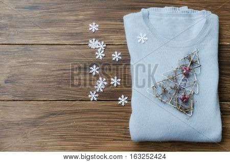Blue Cashmere sweater with decorative tree and snowflakes on wooden background. Concept for Winter time and Christmas. Copy space.
