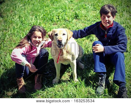 Two Children With Their Big Labrador Dog