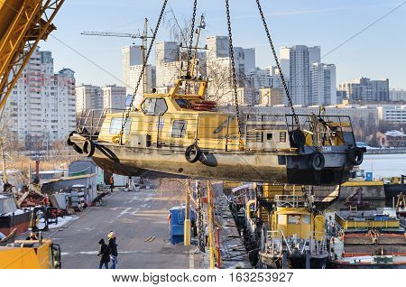 MOSCOW, RUSSIA - NOVEMBER 11, 2016: State Unitary Enterprise Mosvodostok performs recovery vessels on coastal winter parking. River boat carries a crane on four chain slings.