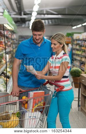 Couple With Grocery List In Supermarket
