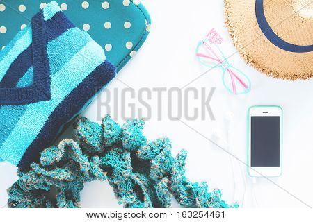 flat lay feminine clothes and accessories collage with t-shirt polka dot bag scarf fashion glasses hat with mobile phone and earphone on white background. Green color concept
