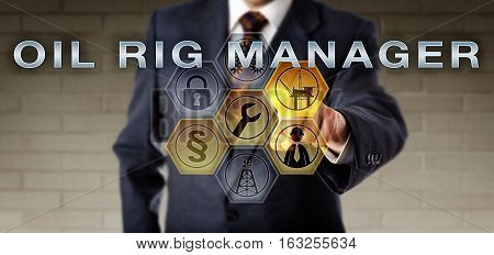 Businessman is activating the term OIL RIG MANAGER on an interactive control monitor. Oil and gas industry metaphor for the role of a supervisor overseeing the operations and crew on an oil rig.