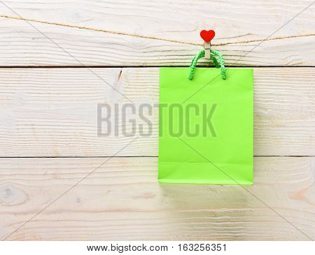 lime green colorful package with present or gift hanging on clothesline on white vintage wooden background copy space