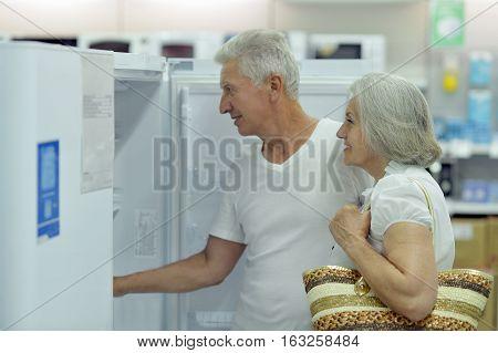 mature couple at electronics shop, choosing goods