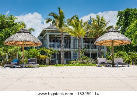Le Morne Mauritius - December 7 2015: Le Morne Beach bungalows and straw beach umbrella palapa in tropical garden on southern coast of Mauritius Island.