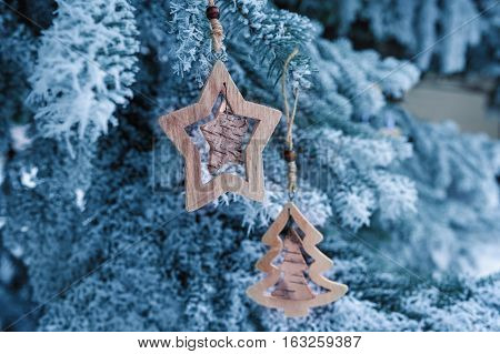 wooden Christmas toys on a beautiful snowy fir tree in winter.