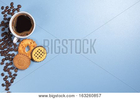 Cup of hot coffee and various cookies on blue background top view. Space for text