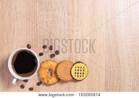Cup of hot coffee and different sweet cookies on wooden table top view. Space for text
