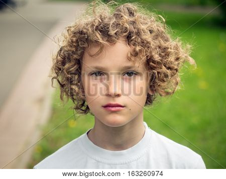 Portrait of a curly-haired baby on natural background