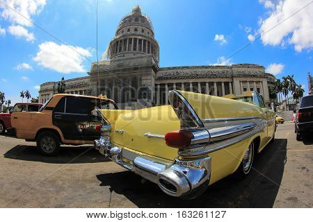 Classic old American yellow car in front of El Capitolio. Classic cars are still in use in Cuba and old timers have become an iconic view and a worldwide known attraction.